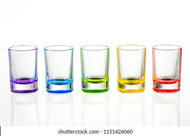 Five multicolored empty shot glasses placed symmetrically on a white background. Conceptual, commercial and advertising photo. Copy space.