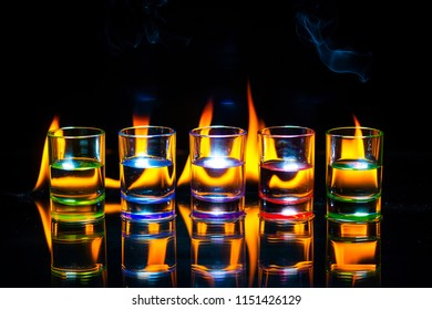 Five multicolored full of drinks shot glasses reflected on the glass surface behind which the flame burns on a black background. Conceptual, commercial and advertising photo. Copy space.