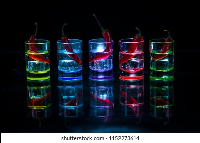 Five multicolored shot glasses full of drink and with the red chili peppers lying inside them symmetrically placed a black background. Conceptual, commercial and advertising photo. Copy space.