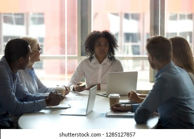 Five multi-ethnic businessman businesswoman gathered together at modern boardroom for planning future projects discussing relevant topics. Black team leader or coach sitting at desk talking with staff