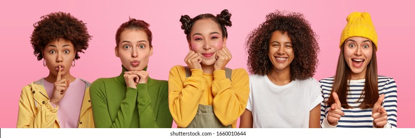 Five multiethnic young women have positive expressions, make hush gesture, point directly at you, smile joyfully, dressed in casual clothes, stand shoulder to shoulder against pink background