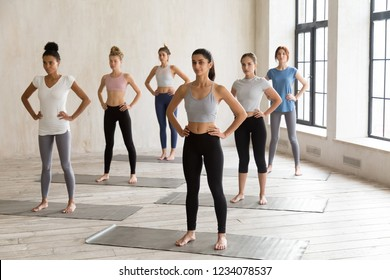 Five multiracial slim females wearing sportswear standing in rows barefoot on rubber black mats ready to start workout at fitness centre. Group training, yoga practising and healthy lifestyle concept