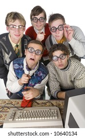 Five nerdy guys sitting in front of old-fashioned computer. They are looking at camera. One of them is pointing at camera. Front view, white background