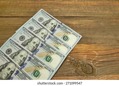 Five New One Hundred Dollar Bill On The Rough Wood Background