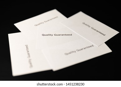 "Five notes with words ""Quality Guaranteed"" are on the black table/background.  World Quality Day"