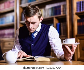 Five oclock tea tradition concept. Young man with antique bookshelves on background. British elite or aristocrats spend leisure in library. Intelligent, man in suit with good manners hold cup of tea.