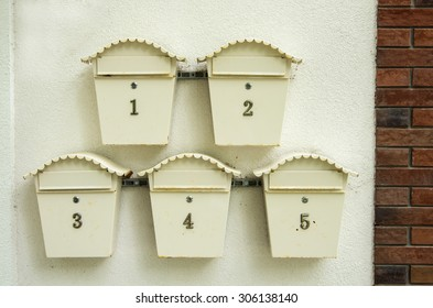 Five old post boxes on the yellow wall