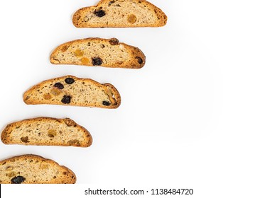 five ong pieces of bright yellow and orange biscotti with white and black sultanas and nuts, dried sweet crispy italian bread On the left part of horizontal shot on the white background with copy spac