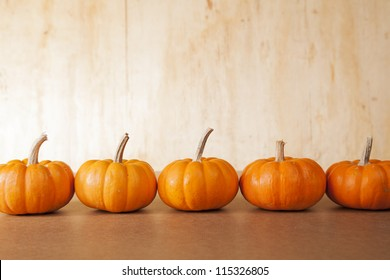 Five orange pumpkins sit in a row in front of a distressed, wooden background.