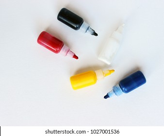 Five paint bottle on textured paper