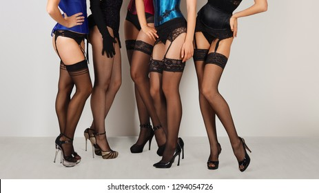 Five pairs of sexy female legs in stockings with suspender belt. Cropped image of cabaret girls in lingerie and corset.