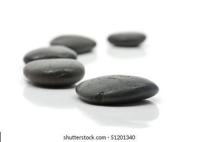Five pebbles forming a bow over white background