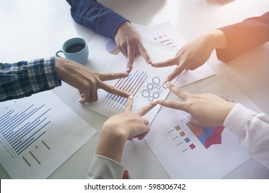 Five people engaged in hand with an asterisk