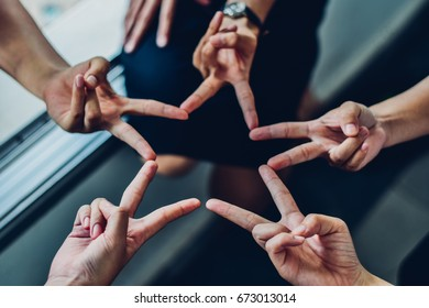 Five people hold their fingers together as a star.Collaborate towards the success of the organization.