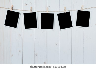 five photo frame blank hanging on wooden board background.