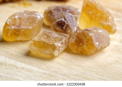 five pieces of brown cane caramel sugar on a wooden substrate, tea party