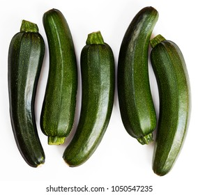 Five pieces of green zucchini (zucchetti, courgettes) on a white background