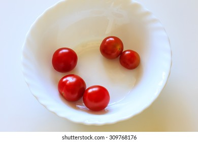 Five plucked from the bush cherry tomatoes in a white bowl on a white table