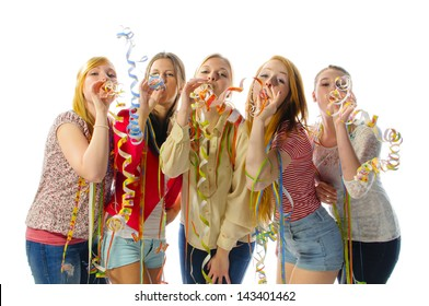 Five pretty teenager girl make party streamers and blow at the camera, isolated against white background.