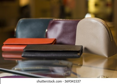 Five purses in different colors lying on a glass shelf in the shop window.