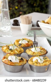 Five quiche appetizers topped with sour cream and chives.