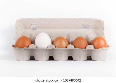 Five raw eggs in carton box isolated on white background. white egg stands out
