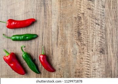 Five red and green chilli pepper on wooden table