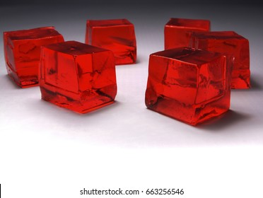 five red jelly cubes closeup, looking like red ice cubes