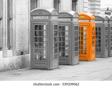 Five Red London Telephone boxes all in a row in the City, in black and white with one booth in orange