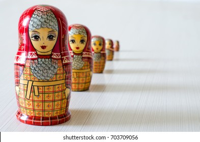 Five red matryoshka. Long shadows. Close-up