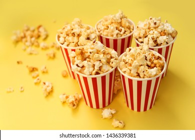 five red-and-white paper cups with popcorn on a yellow background, several pieces are scattered nearby