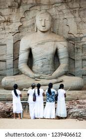 Five religious women are standing and admiring the great Samadhi Statue in Polonnaruwa, Sri Lanka.