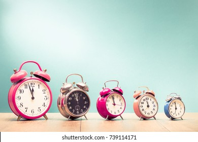 Five retro alarm clocks with last minutes to twelve o'clock on wooden table front gradient mint green wall background. Vintage old style filtered photo
