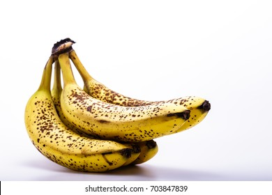 Five ripe bananas with brown spots isolated on a white background