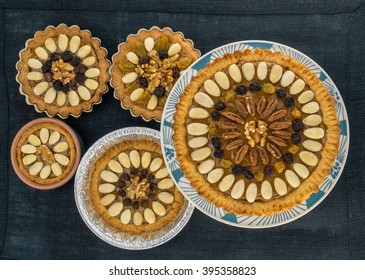 Five round traditional Polish Easter cakes with almonds, raisins and walnuts on the dark fabric background.