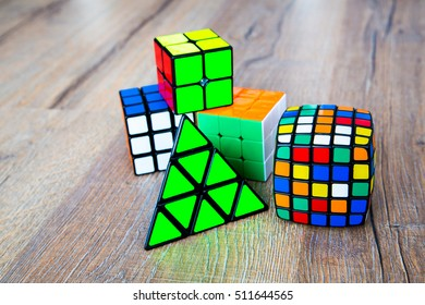 Five Rubik's cube on the wood background. Triangle Rubik's cube, 5x5, 3x3 and 2x2. Difficult quiz tasks. IQ games. Challenge.