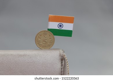 Five Rupee money coin of India and mini Indian flag stick on the leather wallet on grey background. Concept of finance or currency.