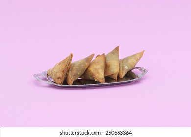 Five samosas on a silver platter on a pink background