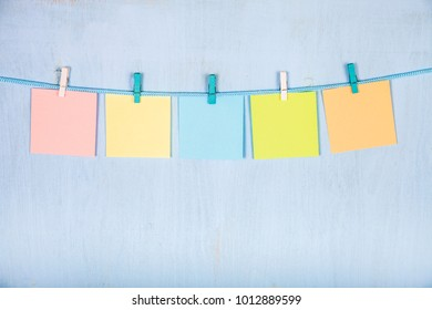Five sheets of paper hang on a rope on a blue wooden background.