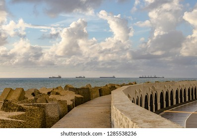 Five ships seen from the outer wall of a harbor, which hosts boat garages. The sun is going down in a rainy day, with heavy numbs and a blue sky