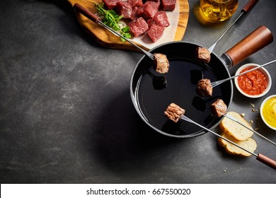 Five skewers with cubes of cooked beef held over fondue pot. Raw meat, bread and sauce on either side.