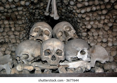 Five skulls with bones in Kutna Hora ossuary, Czech Republic