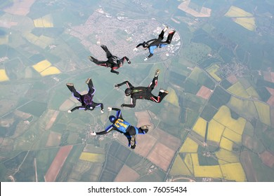 Five skydivers in freefall doing formations