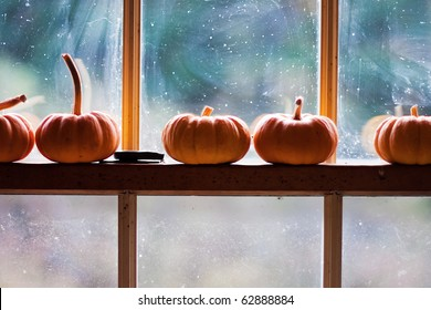 five small pumpkins sitting on a window frame.
