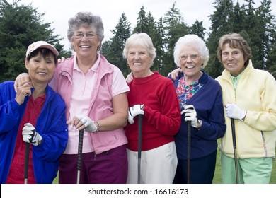 Five smiling elderly golfers holding golf clubs. Horizontally framed photo.