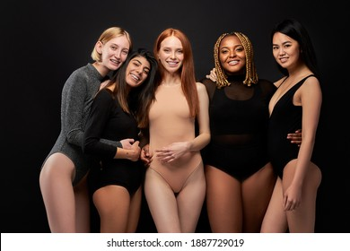 five smiling laughing beautiful women in bodysuit standing together, having fun, look at camera, isolated on black studio background