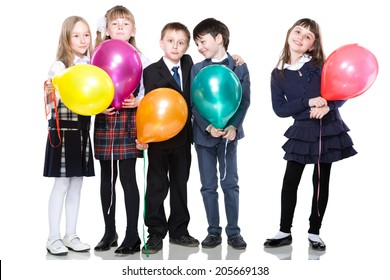 Five smiling schoolchild standing with colorful baloons, isolated on white