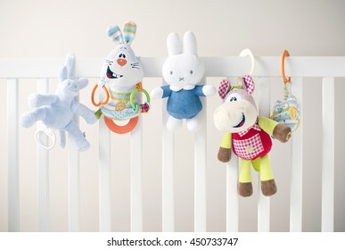 Five soft colorful toys at white children's bed.