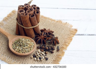 five spices (cinnamon, fennel, star anise, pepper, clove) to make chinese five-spice powder on wooden background.