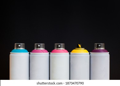 Five spray cans of graffiti paints on a black background: blue, pink, magenta, yellow and purple.